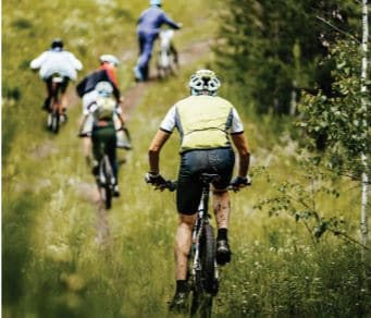 Cyclists Cycling Through The Grass